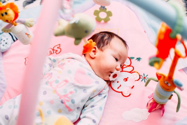 Adorable infant lying on colorful baby play mat with toys. Photo ...