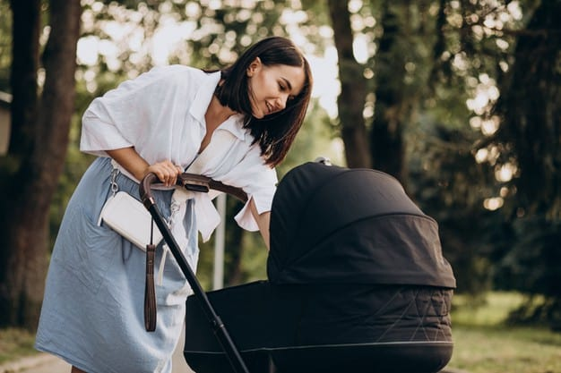 mother having a best stroller and walking in park with her baby