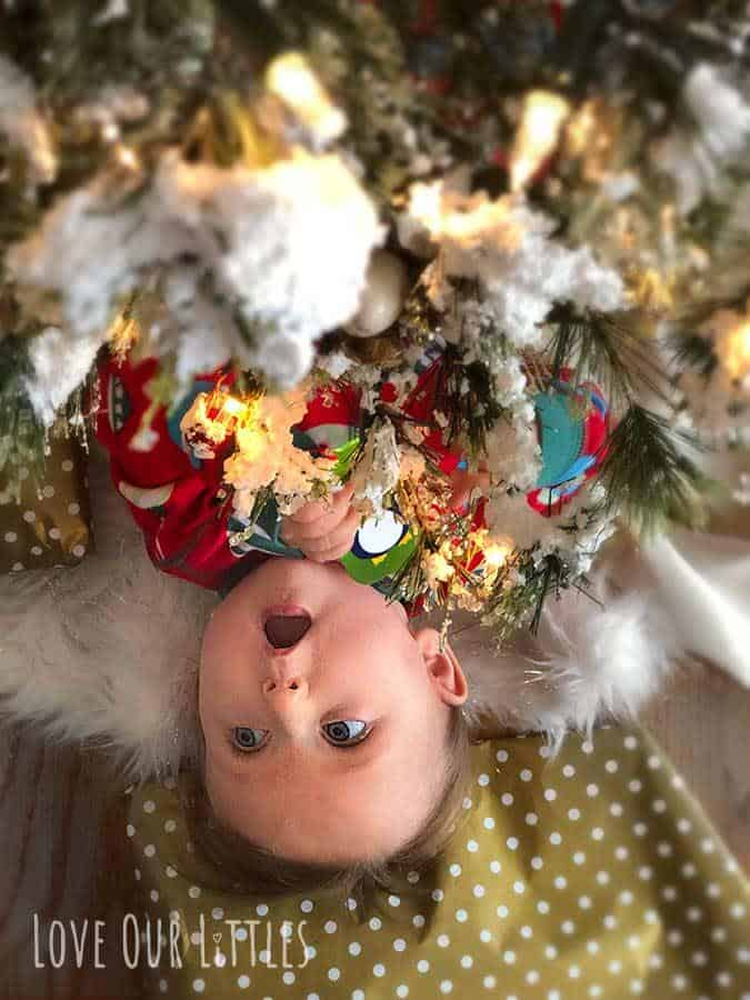 """Baby peeking out from under a Christmas tree with cute """"open-mouth"""" expression."""