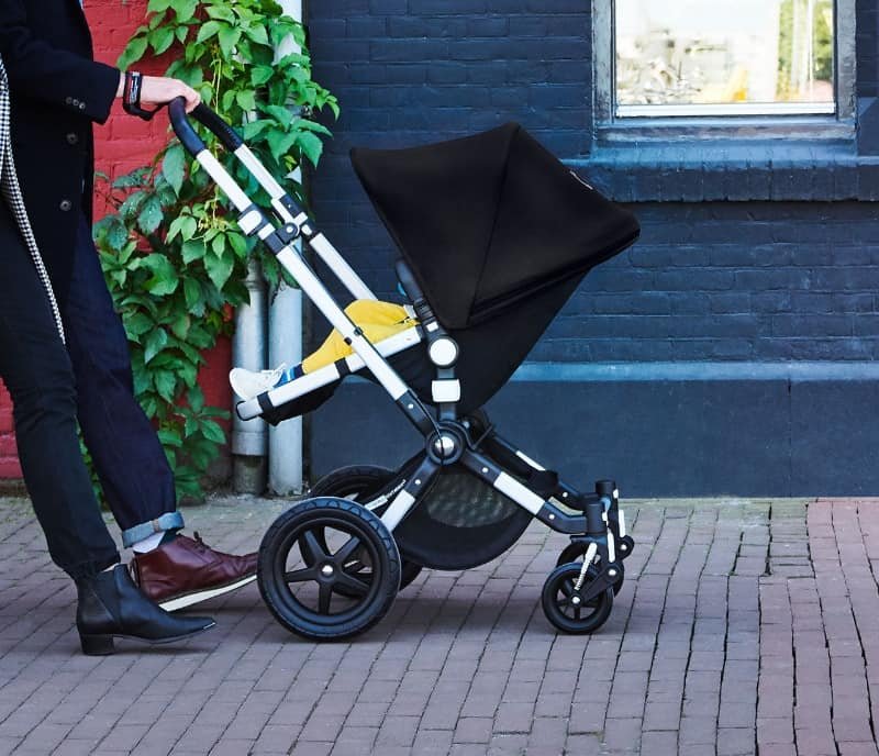 Two people and a child strolling on the street with their Bugaboo Cameleon 3 Plus pushchair.