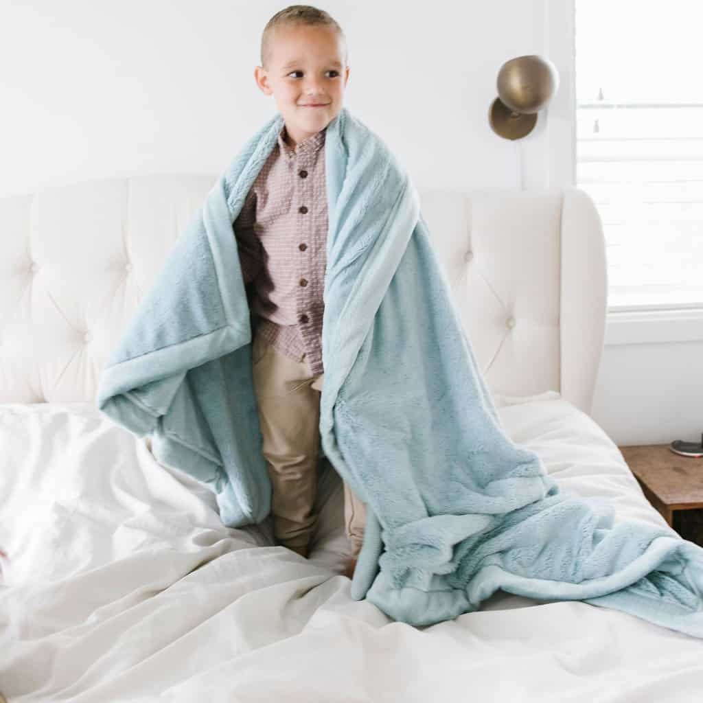 A cozy blanket from godparent is a practical gift for baptism