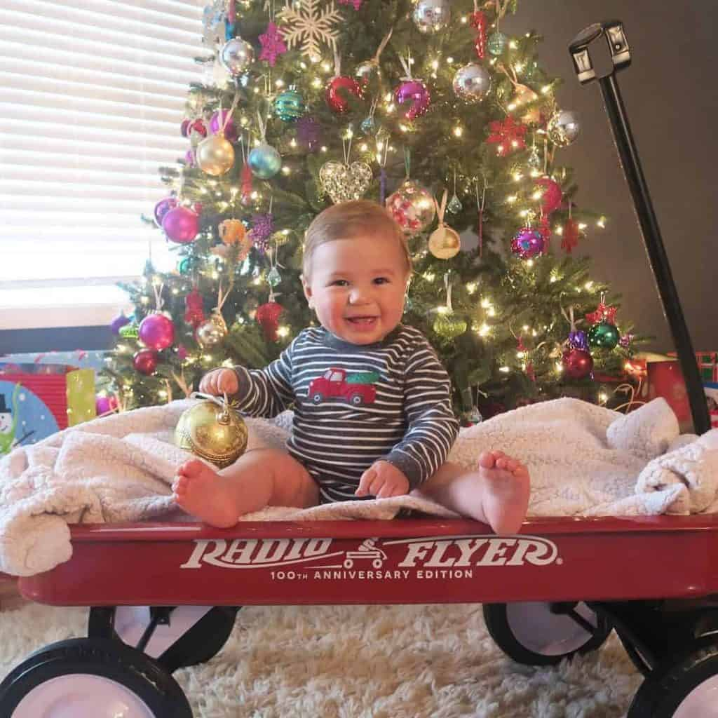 A baby or toddler sitting in a red wagon is one of those classic Christmas picture ideas.