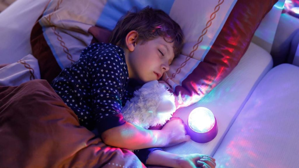 Young boy falling asleep with best night light projector - Best Baby Projectors to Make Wonderful Baby Light Shows - Baby Journey Blog